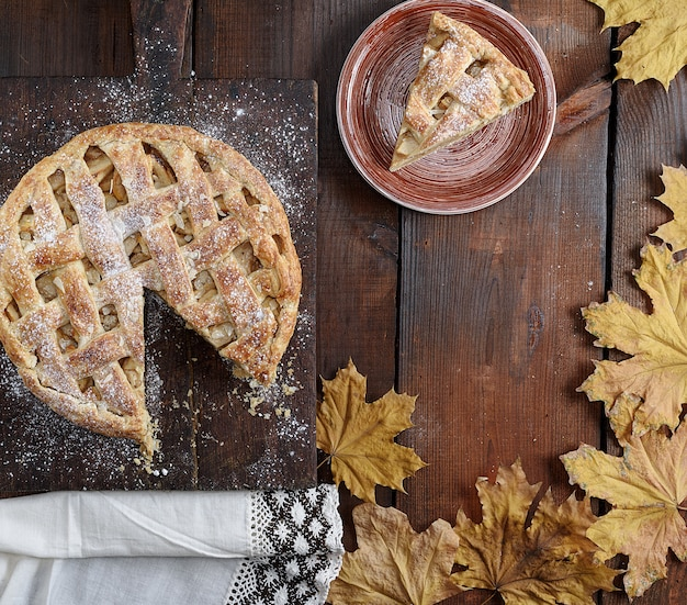 Torta di mele rotonda al forno e un pezzo tagliato su un piatto