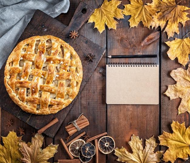 Torta di mele rotonda intera al forno su un bordo di legno marrone, pasta sfoglia