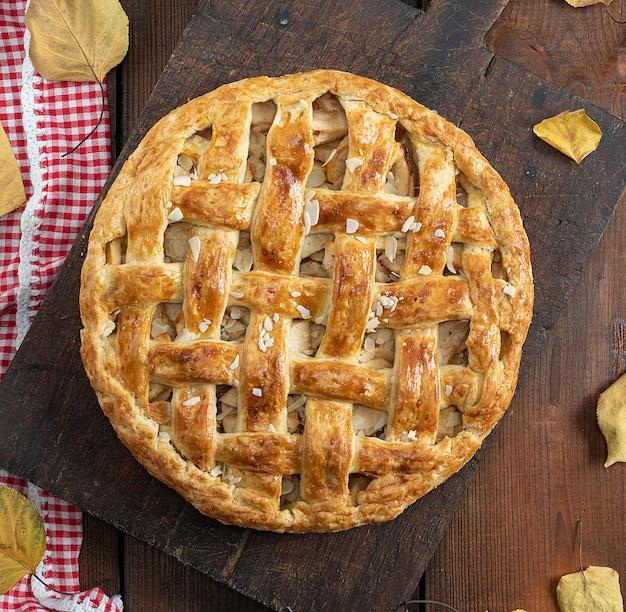 Torta di mele rotonda intera al forno su un bordo di legno marrone