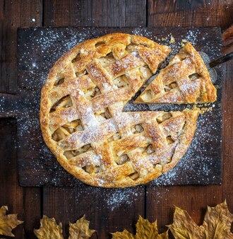 Torta di mele rotonda intera al forno su un tagliere marrone vecchio rettangolare cosparso di zucchero a velo