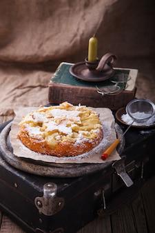 Torta di mele su una valigia vintage in zucchero a velo