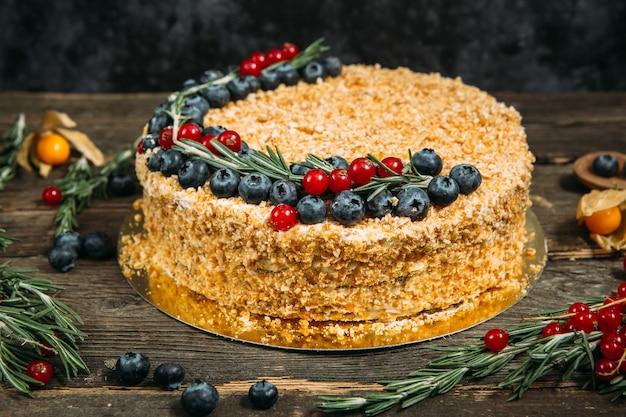 Torta di miele appetitosa dolce gourmet con frutti di bosco