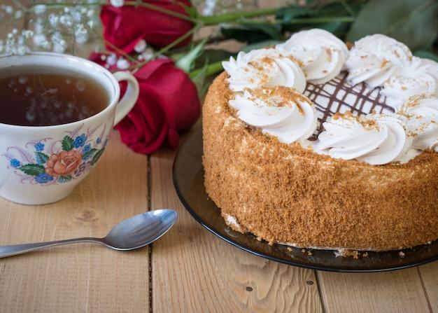 Torta di miele con fiori e tè su un tavolo di legno