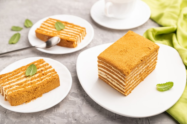 Torta di miele fatta in casa con crema di latte e menta con una tazza di caffè su un tavolo di cemento grigio