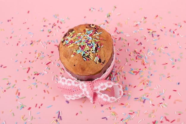 Torta di pasqua con spruzza brillante sul tavolo rosa
