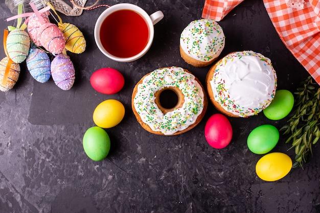 Torta di pasqua e uova colorate su uno sfondo scuro