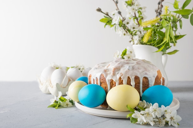 Torta di pasqua, uova colorate sul tavolo della famiglia di eventi con fiori di ciliegio. spazio per il testo