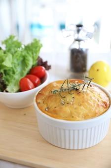 Torta di pastore fatta in casa, purè di patate con pancetta tritata e carne di maiale e insalata