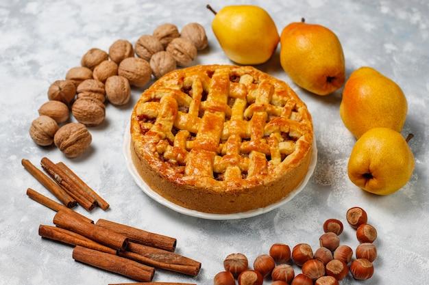Torta di pere fatta in casa con cannella e noci su luce