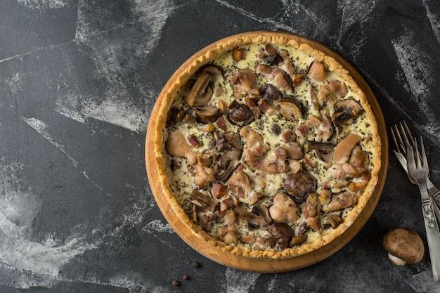 Torta di quiche ai funghi con champignon e formaggio su sfondo scuro