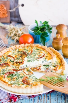Torta di quiche francese casalinga affettata con il pomodoro, il formaggio e l'erba su un piatto.