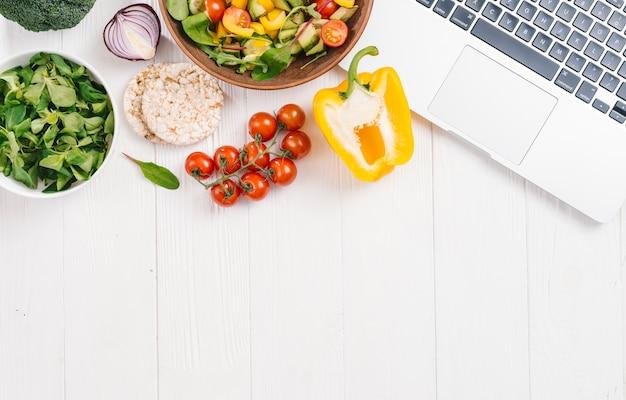 Torta di riso soffiato; insalata di verdure e insalata di mais fresco lascia con un computer portatile aperto sulla scrivania bianca