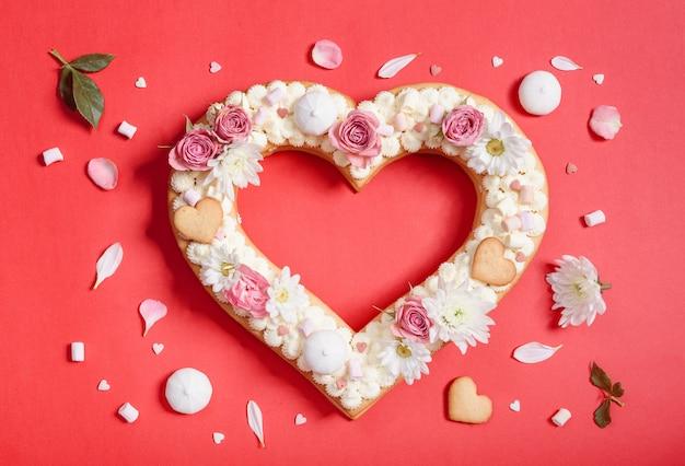 Torta di san valentino a forma di cuore con fiori come decorazione.