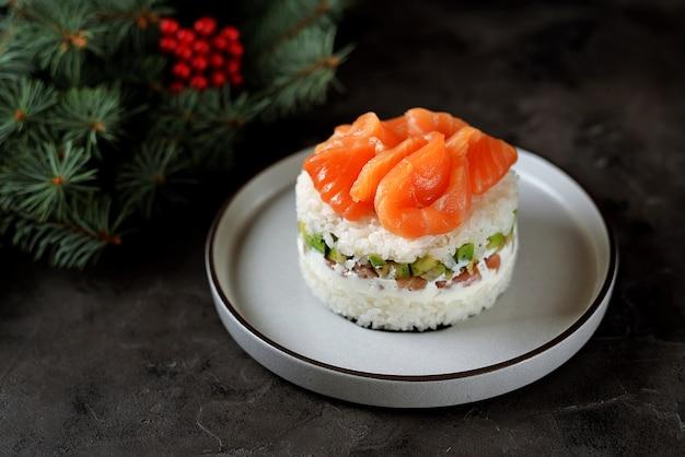 Torta di sushi fatta in casa con salmone leggermente salato, avocado, formaggio morbido e alghe. superficie di natale.