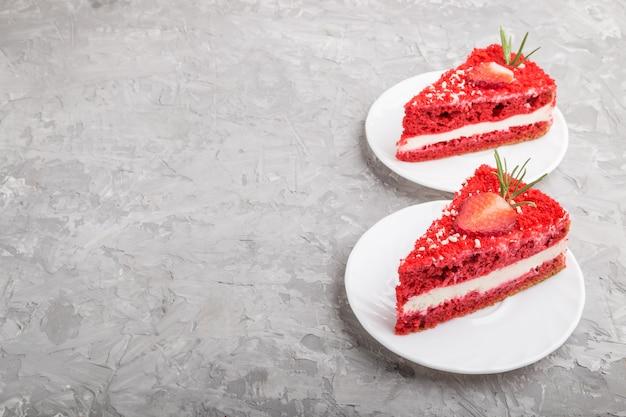 Torta di velluto rosso fatto in casa con crema di latte e fragola su uno sfondo grigio