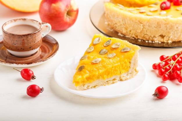 Torta di zucca dolce americana tradizionale decorata con bacche rosse e semi di zucca con una tazza di caffè su un fondo di legno bianco.