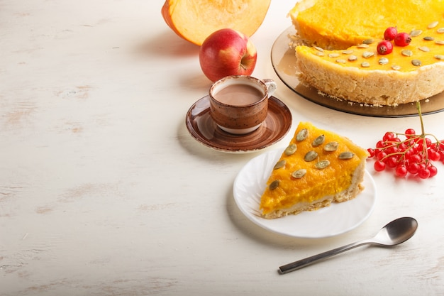 Torta di zucca dolce americana tradizionale decorata con le bacche e i semi di zucca rossi del biancospino con la tazza di caffè su un bianco di legno. vista laterale.