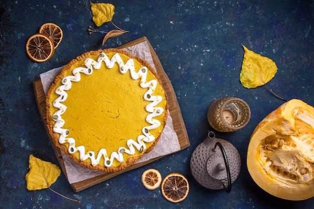 Torta di zucca rotonda deliziosa speziata decorata con crema bianca e semi di zucca