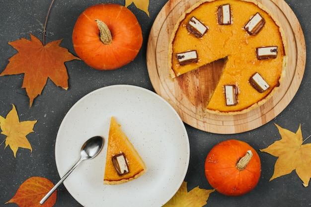 Torta di zucca su una tavola di legno rotonda, un pezzo di torta su un piatto bianco foglie di autunno e piccole zucche.