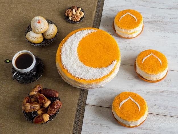 Torta dorata fatta in casa con una luna crescente, servita con caffè nero e datteri. muro di ramadan