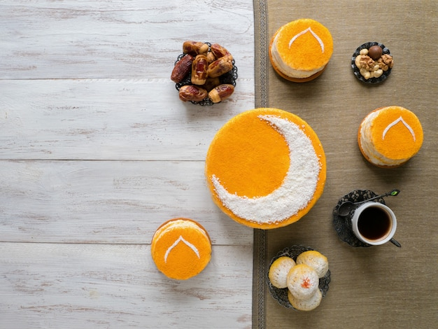 Torta dorata fatta in casa con una luna crescente, servita con caffè nero e datteri. ramadan wall, copia spazio