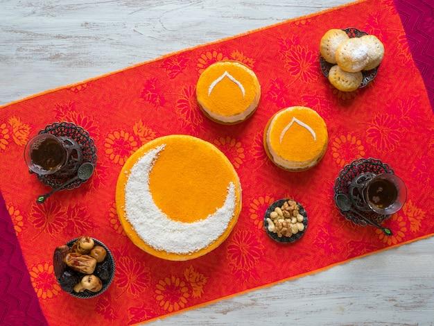 Torta dorata fatta in casa con una luna crescente, servita con una tazza di tè e datteri. muro di ramadan
