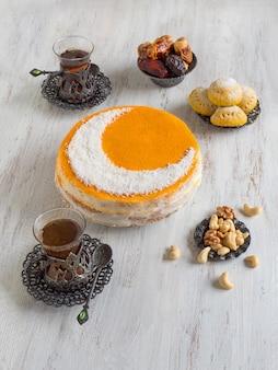 Torta dorata fatta in casa con una luna crescente, servita con una tazza di tè e datteri. tavolo ramadan