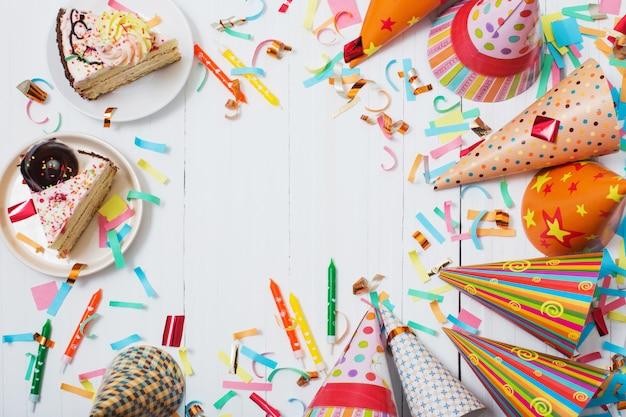 Torta e decorazione di compleanno su fondo di legno bianco