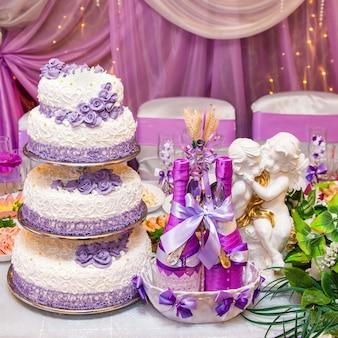 Torta e due bottiglie di vino su una tavola di nozze decorata