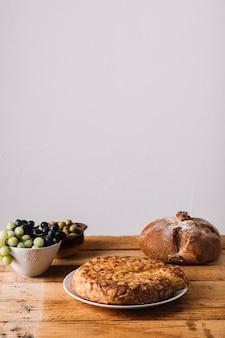 Torta e pane vicino a uva e olive