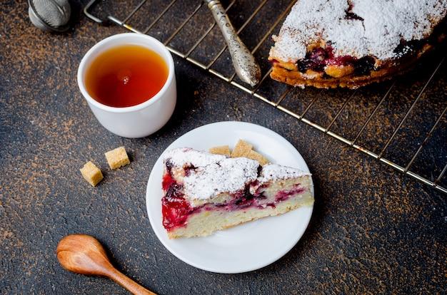 Torta e tè della frutta su una tavola di legno