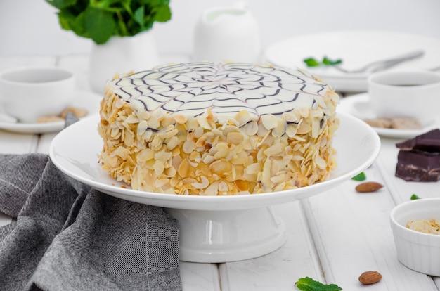 Torta esterhazy ungherese tradizionale su un piatto bianco su un tavolo di pietra con una tazza di caffè, menta e mandorle.