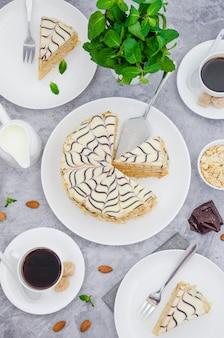 Torta esterhazy ungherese tradizionale su un piatto bianco su uno sfondo di pietra con una tazza di caffè, menta e mandorle.
