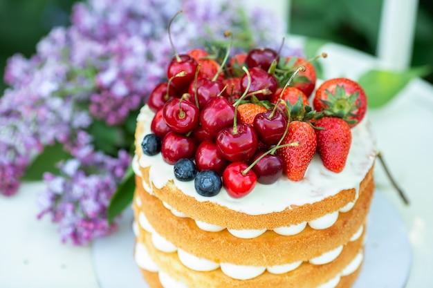 Torta estiva fatta in casa biscotto con crema e frutti di bosco freschi nel giardino