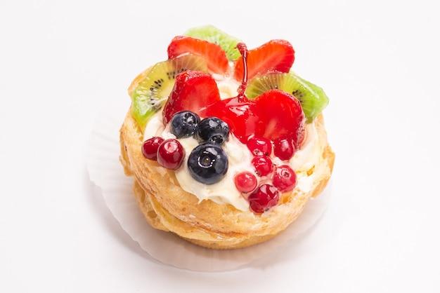 Torta fatta casa con crema e frutti isolati.