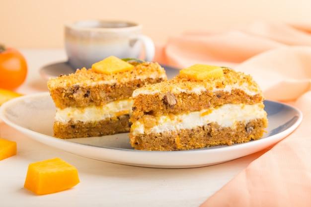 Torta fatta in casa con cachi e zucca su uno sfondo di legno con tessuto arancione