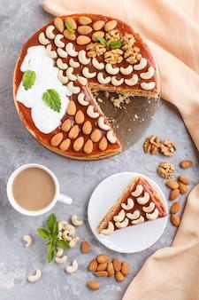 Torta fatta in casa con crema al caramello e noci con una tazza di caffè sul cemento grigio