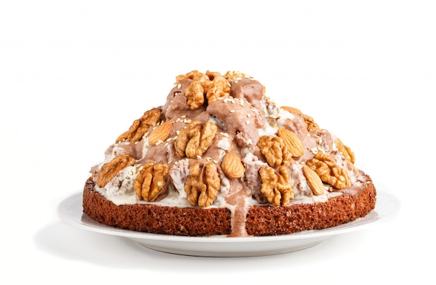 Torta fatta in casa con crema di latte cacao mandorle nocciole isolato su sfondo bianco