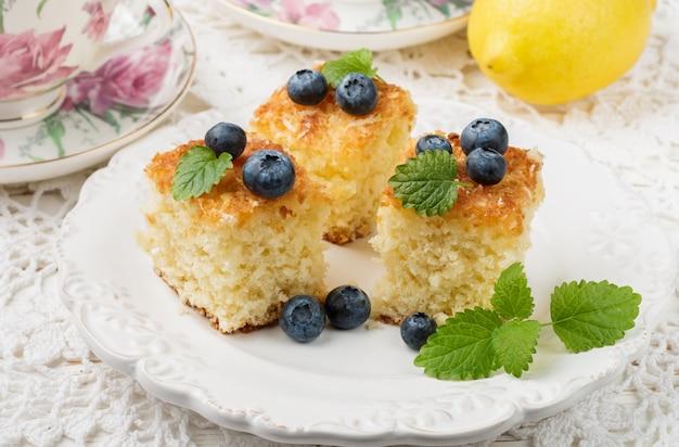 Torta fatta in casa per tè con mirtilli di cocco, limone e frutti di bosco freschi, stile rustico,