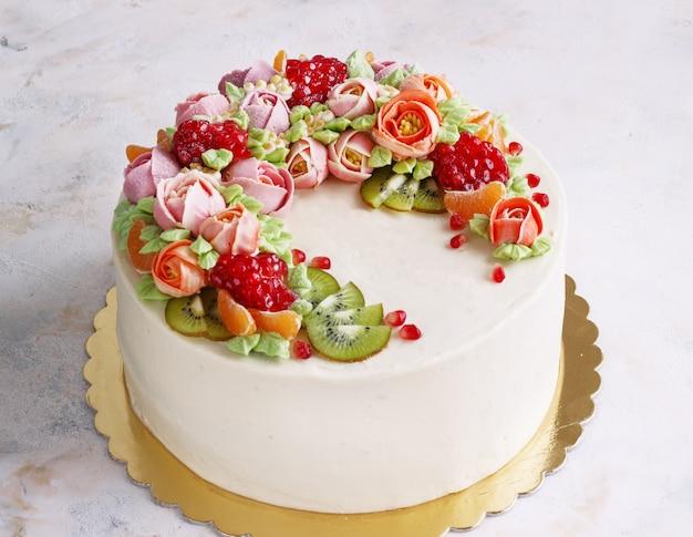 Torta festiva con crema di fiori e frutti su una luce