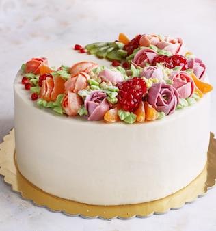 Torta festiva con crema di fiori e frutti su una superficie leggera