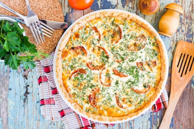 Torta francese fatta in casa della quiche con il pomodoro, il formaggio e l'erba su un piatto su una tavola di legno. vista dall'alto