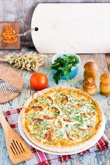 Torta francese fatta in casa della quiche con il pomodoro, il formaggio e l'erba su un piatto su una tavola di legno