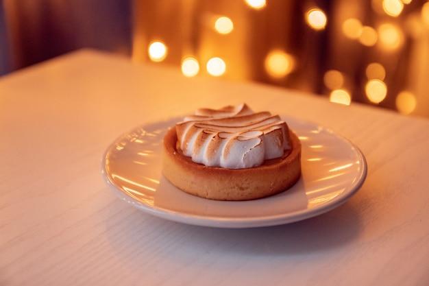 Torta fresca con crema aerata su un piatto di ceramica bianco