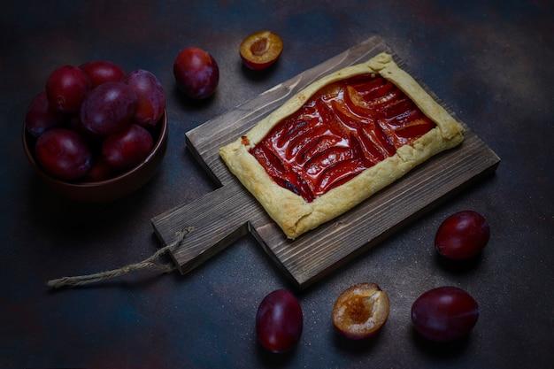 Torta fresca di galette di prugne con prugne crude su oscurità