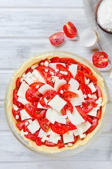Torta greca grezza con feta e pomodori per cottura