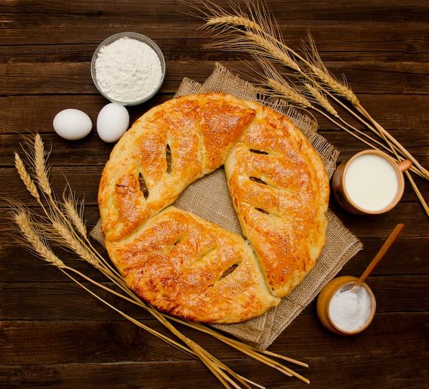 Torta, ingredienti per la cottura, spighe di grano e tazza di latte. vista dall'alto