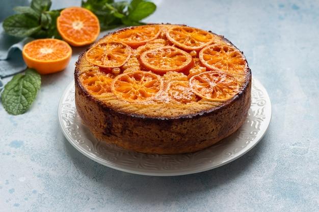 Torta inversa del mandarino su una pietra o su un cemento celeste