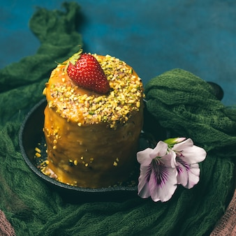 Torta lustrata del caramello con la decorazione del fiore della fragola su fondo scuro con la tessile.