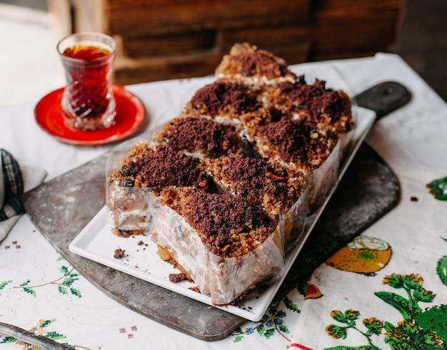 Torta marrone affettata squisita deliziosa in polvere all'interno del piatto bianco con tè caldo